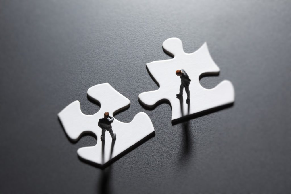 San Diego, California, USA - July 25, 2011: Two Preiser businessman figurines standing on blank puzzle pieces illustrating the concepts of problem solving and negotiation. Shot in a studio setting.
